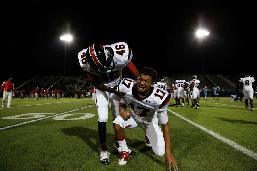 Spring Westfield's Derek Wiley (46) helps up Jason Reid (17) after losing to Skyline.