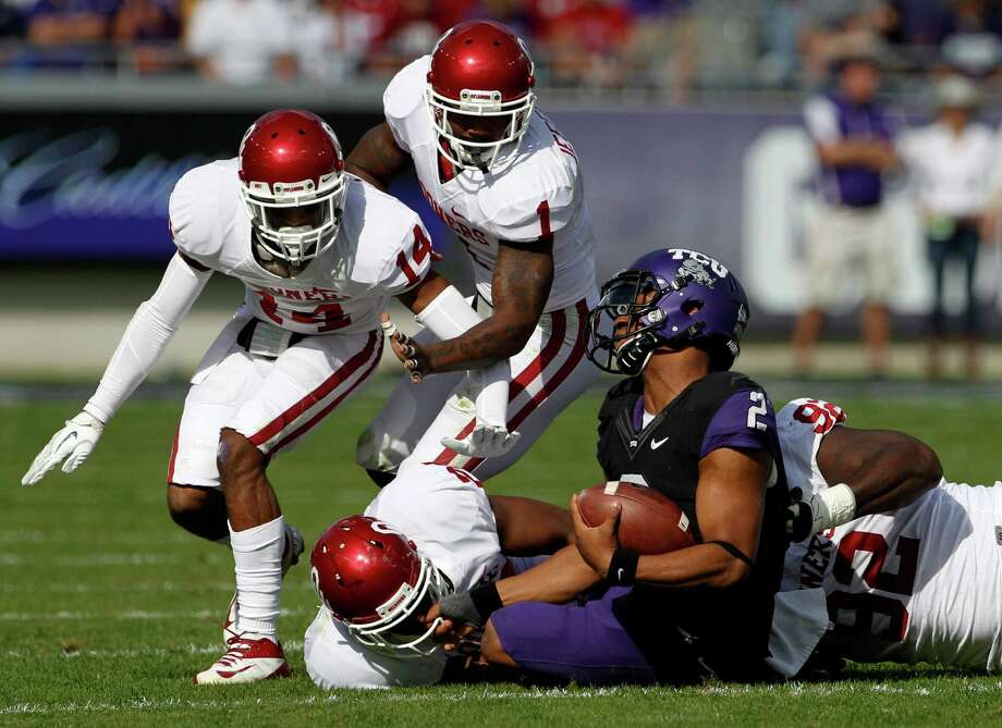 The Oklahoma defense, which held TCU to 11 first downs, swarms to quarterback Trevone Boykin. Photo: Tony Gutierrez, STF / AP