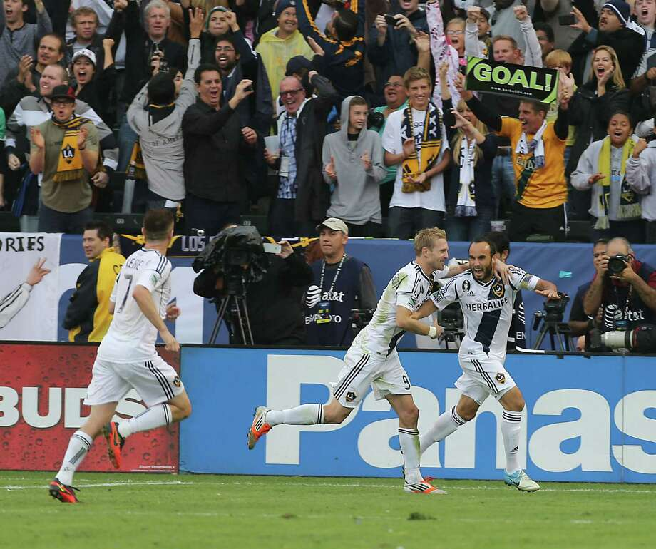 The Los Angeles Galaxy midfielder Landon Donovan right, celebrates with teammte Chad Barrett center as the Los Angeles Galaxy forward Robbie Keane left, looks on after Donovan scored a goal during the second half of the 2012 MLS Cup championship game against the Houston Dynamo at the Home Depot Center Saturday, Dec. 1, 2012, in Los Angeles. Photo: James Nielsen, Chronicle / © Houston Chronicle 2012