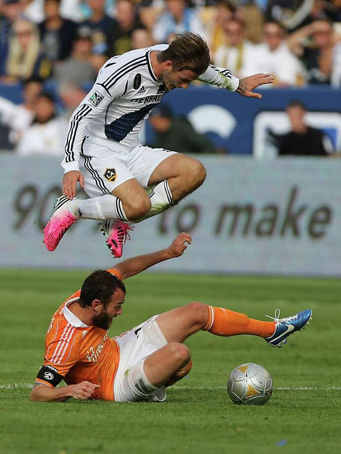 The Los Angeles Galaxy David Beckham jumps over the Houston Dynamo midfielder Brad Davis (11) during the first half of the 2012 MLS Cup championship game at the Home Depot Center Saturday, Dec. 1, 2012, in Los Angeles. Photo: James Nielsen, Chronicle / © Houston Chronicle 2012