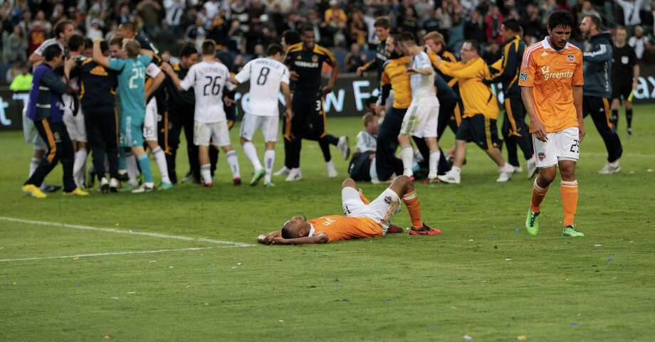 The Houston Dynamo Ricardo Clark lies on the field as teammate Brian Ching walks towards him after the Dynamo were defeated in the 2012 MLS Cup championship game by the Los Angeles Galexy at the Home Depot Center Saturday, Dec. 1, 2012, in Los Angeles. Photo: James Nielsen, Chronicle / © Houston Chronicle 2012