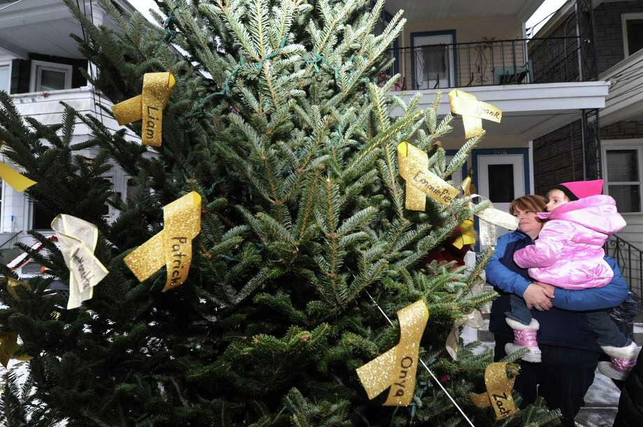 Rathbone family friend Vikki O'Connor and her 2-year-old daughter Grace of Glenville look over the  decorated tree in honor Ila Jean who died in April from childhood cancer in Schenectady, NY Thursday Dec. 1, 2012. (Michael P. Farrell/Times Union) Photo: Michael P. Farrell