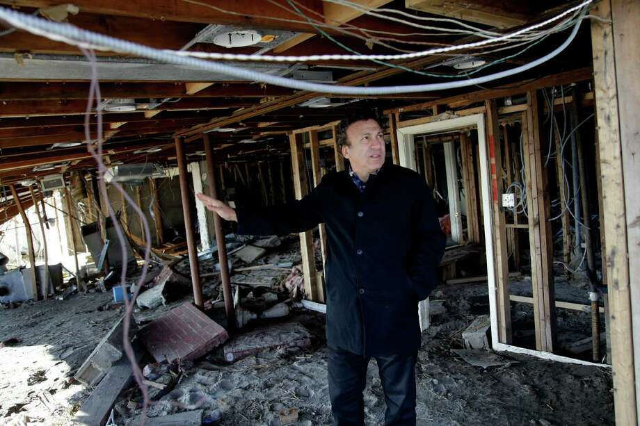 Albert Negri talks with contractors in the basement of his home, which was damaged by Superstorm Sandy, on the Rockaway Peninsula in New York, Thursday, Nov. 29, 2012.  Sandy damaged or destroyed  305,000 housing units in New York.  (AP Photo/Seth Wenig) Photo: Seth Wenig