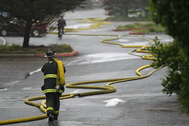 A firefighter collects hoses used to put out a fire at the historic Fleishhacker Pool in the San Francisco Zoo on December 1, 2012. Photo: Rashad Sisemore, The Chronicle