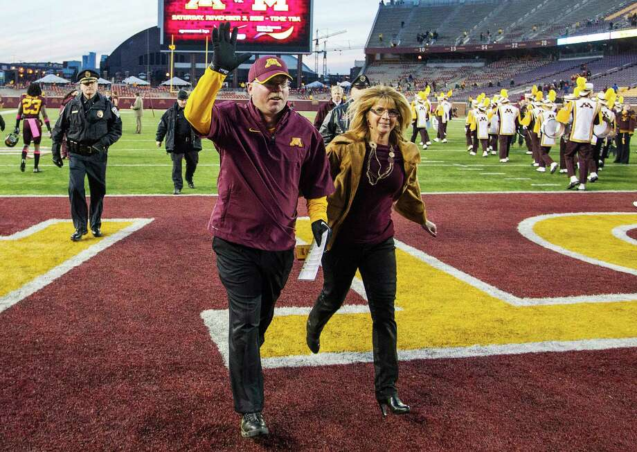 ADVANCE FOR WEEKEND EDITIONS, DEC. 1-2 - FILE - In this Oct. 27, 2012, file photo, Minnesota head coach Jerry Kill raises his hands to the fans as he runs off the field with his wife Rebecca after beating Purdue in an NCAA college football game in Minneapolis. Kill hasn't let epilepsy keep him from climbing college football's coaching ladder to the Big Ten level with Minnesota, (AP Photo/Jesse Johnson, File) Photo: Jesse Johnson