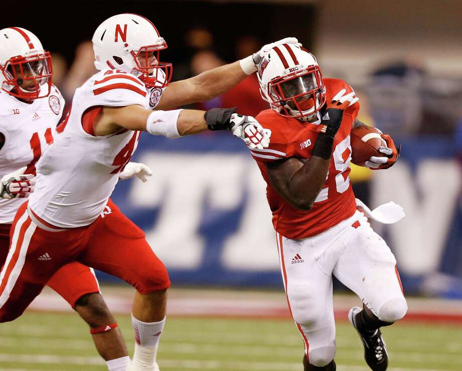 INDIANAPOLIS, IN - DECEMBER 01: Montee Ball #28 of the Wisconsin Badgers tries to get around the tackle of Sean Fisher #42 of the Nebraska Cornhuskers during a second quarter run during the Big 10 Conference Championship Game at Lucas Oil Stadium on December 1, 2012 in Indianapolis, Indiana. Photo: Gregory Shamus, Getty Images / 2012 Getty Images