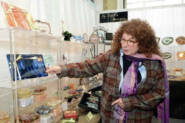 Susan Lowenthal, of Westport, points to a cheese board for sale at her booth, By Susan Designs, at the SoNo Market Place, an indoor European style market located at 314 Wilson Avenue in Norwalk on Saturday, Dec. 1, 2012. Lowenthal is a mixed media artist who incorporates petrified wood, agate, and stones into her work. Photo: Amy Mortensen / Connecticut Post Freelance