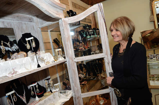 Janet Falkenthal, of the Fashion Exchange consignment shop in Newtown, looks over treasures for sale at her booth at the SoNo Market Place, an indoor European style market located at 314 Wilson Avenue in Norwalk on Saturday, Dec. 1, 2012. Photo: Amy Mortensen / Connecticut Post Freelance