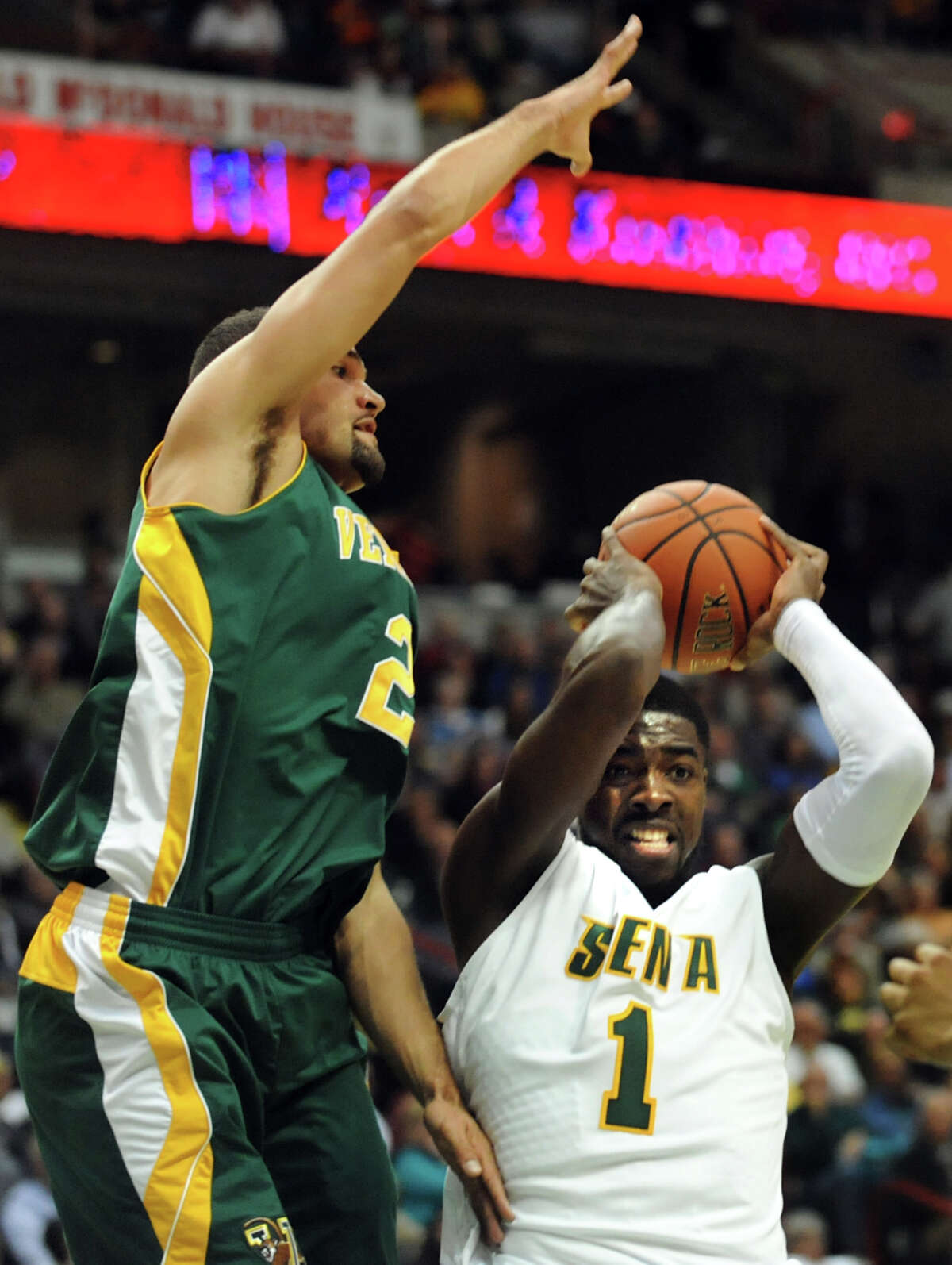 Siena's O.D. Anosike (1), right, gets the rebound as Vermont's Luke Apfield (2), left, defends during their basketball game on Friday, Nov. 9, 2012, at Times Union Center in Albany, N.Y. (Cindy Schultz / Times Union)