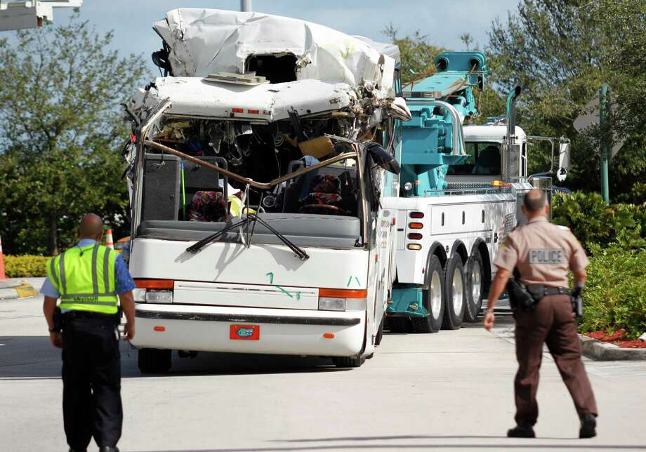 Law enforcement officers watch as a bus which hit a concrete overpass at Miami International Airport is hauled away, Saturday, Dec. 1, 2012 in Miami. The vehicle was too tall for the 8-foot-6-inch entrance to the arrivals area, and buses are supposed to go through the departures area which has a higher ceiling, according to an airport spokesperson. (AP Photo/Wilfredo Lee) (AP Photo/Wilfredo Lee) Photo: Wilfredo Lee
