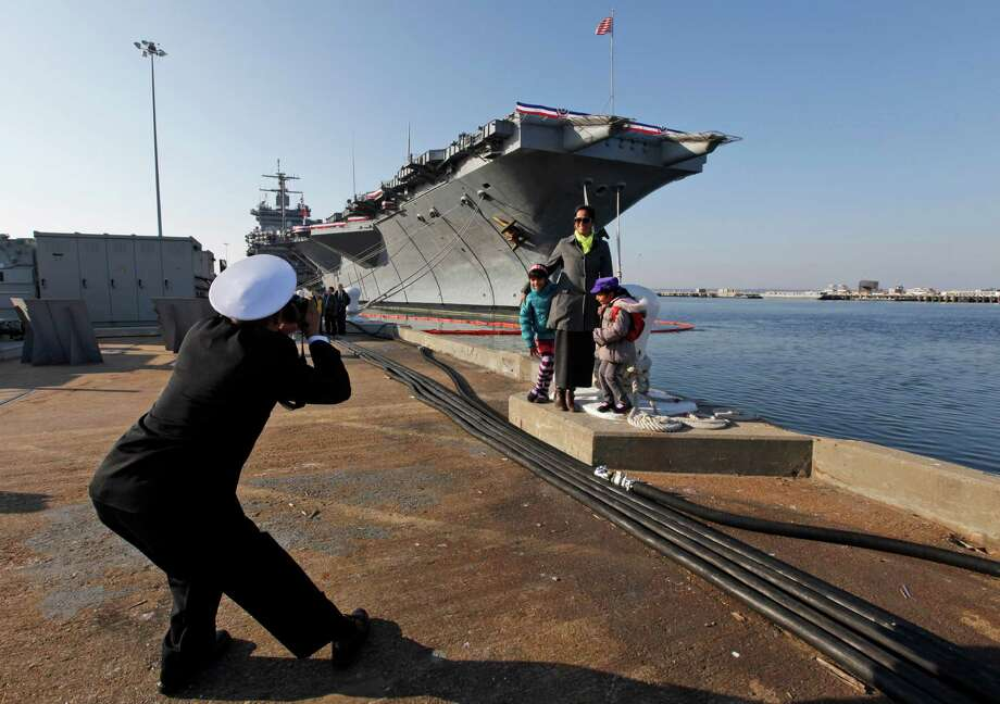 Senior Chief Nageer Rahim, originally from Guyane, photographs his wife, Aliya and their kids in front of the USS Enterprise after an inactivation ceremony for the first nuclear powered aircraft carrier USS Enterprise at Naval Station Norfolk  Saturday, Dec. 1, 2012 in Norfolk, VA.   The ship served in the fleet for 51 years.  (AP Photo/Steve Helber) Photo: Steve Helber