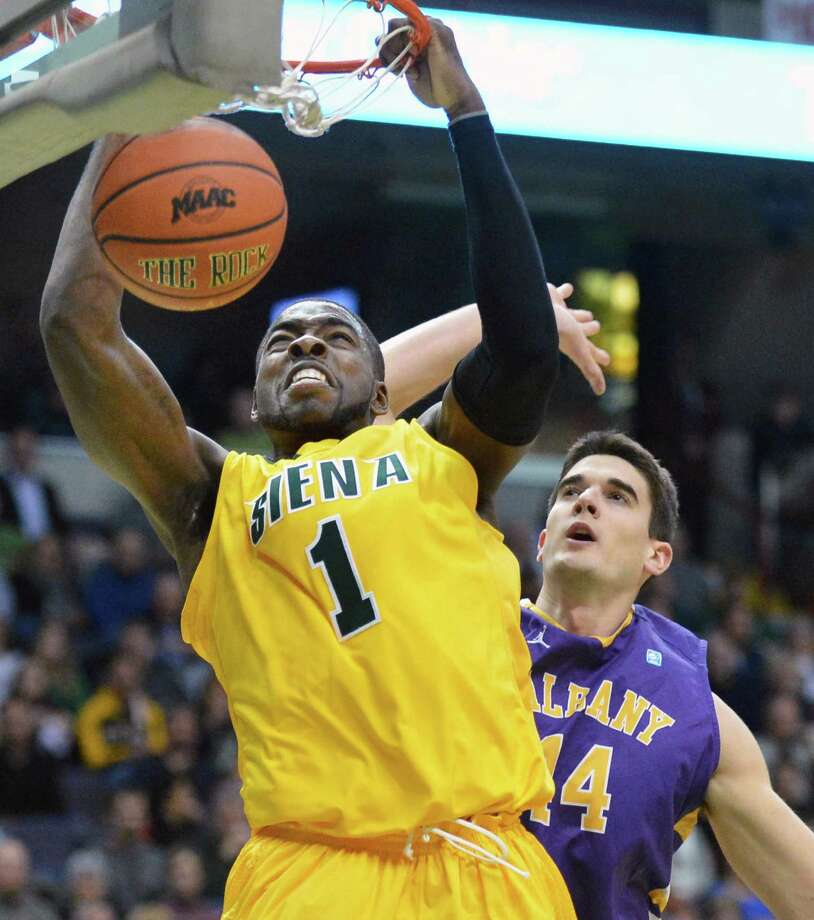 Siena's #1 O.D.Anosike slam dunks as UAlbany's #44 John Puk tries to defend during Saturdays game at the Times Union Center in Albany Dec. 1, 2012.  (John Carl D'Annibale / Times Union) Photo: John Carl D'Annibale / 00020104A