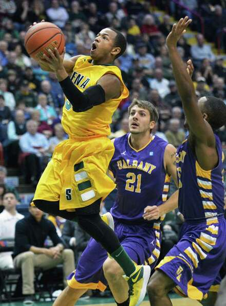 Siena's #5 Evan Hymes, left, goes to the hoop  during Saturdays game against UAlbany at the Times Un