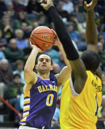 UAlbany's #0 Jacob Iati, shoots from the outside as Siena's #1 O.D.Anosike, at right, covers during