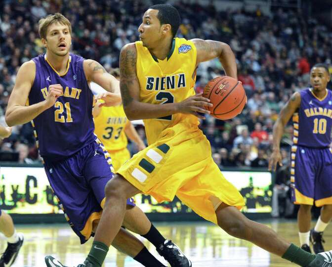 Siena's #2 Trenity Burdine makes his move to the basket as UAlbany's #21 Blake Metcalf defends durin