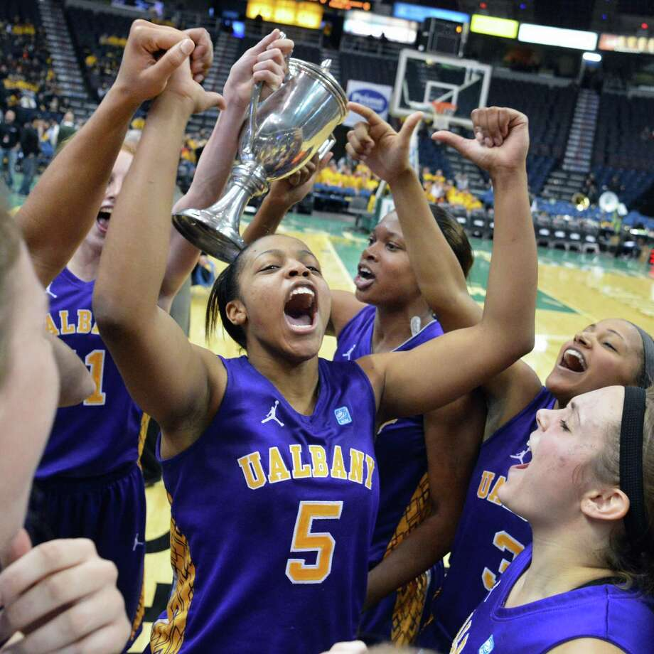 UAlbany's #5 Ebome Henry, center, and teammates cheer as they hoist the Albany Cup high after defeating Siena Saturday at the Times Union Center in Albany Dec. 1, 2012.  (John Carl D'Annibale / Times Union) Photo: John Carl D'Annibale / 00020278A