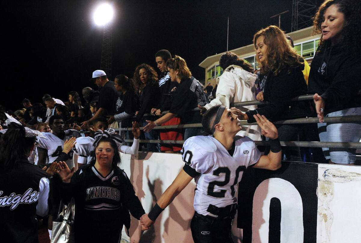 Steele receiver Matthew Mayle (20) holds the hand of his sister, cheerleader Lindsay Mayle, as they greet fans and family after Steele defeated Edinburg North in Class 5A Division II football playoffs action in Kingsville on Saturday, Dec. 1, 2012.