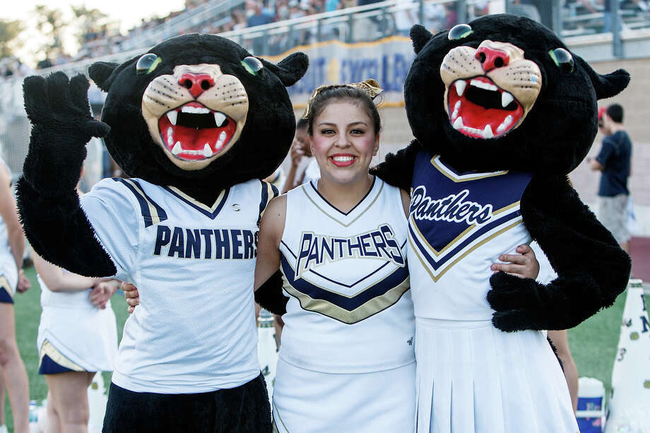 O'Connor cheerleader Issys Garcia poses with mascots Pauly-D and Paulina during their Class 5A Division II third round game with Laredo Alexander at Farris Stadium on Dec. 1, 2012.  O'Connor won the game 44-24.  MARVIN PFEIFFER/ mpfeiffer@express-news.net Photo: MARVIN PFEIFFER, Express-News / Express-News 2012