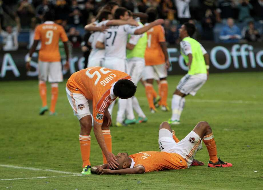 The Dynamo's Brian Ching, a substitute in the 77th minute, tries to console teammate Ricardo Clark as some of the Los Angeles Galaxy celebrate their victory. Photo: James Nielsen, Staff / © Houston Chronicle 2012