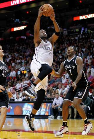 Miami Heat guard Dwyane Wade (3) goes up for a shot against Brooklyn Nets forward Kris Humphries (43) and guard Joe Johnson (7) during the first half of an NBA basketball game, Saturday, Dec. 1, 2012 in Miami. Wade scored a season-high 34 points as the Heat defeated the Nets 102-89. (AP Photo/Wilfredo Lee) Photo: Wilfredo Lee