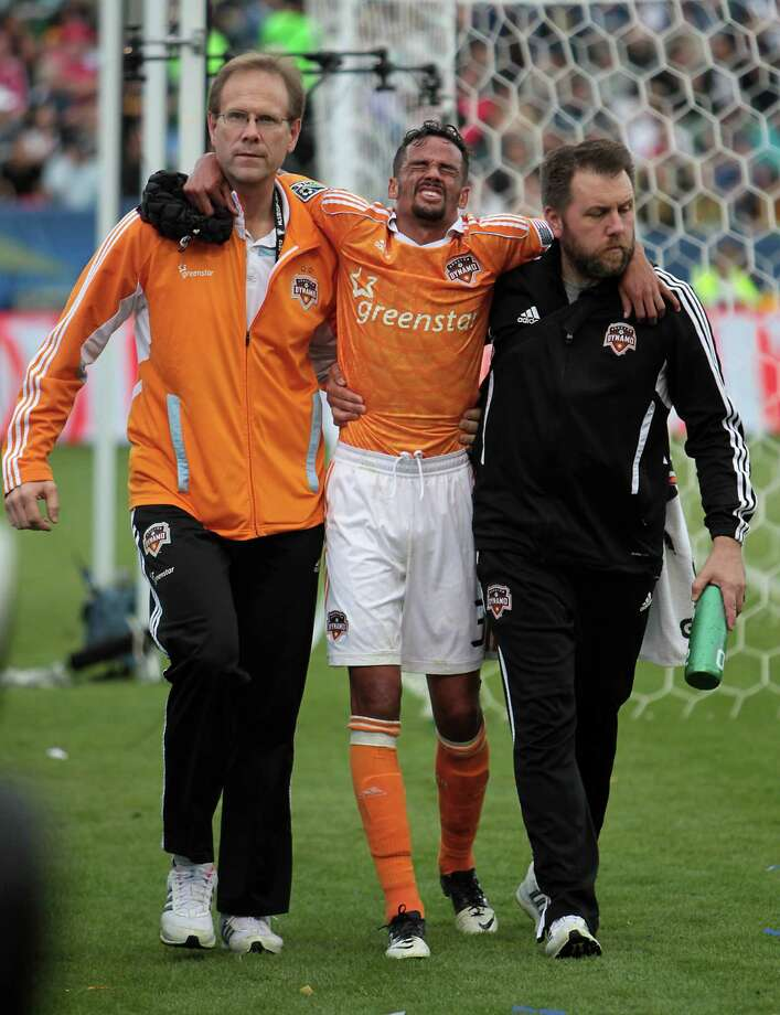 Forward Calen Carr, center, who gave the Dynamo the lead in the 44th minute, is helped off the field after injuring his left knee in the second half. Photo: James Nielsen, Staff / © Houston Chronicle 2012