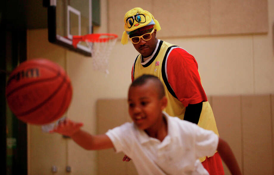 Streetballer Craig McArthur offers guidance to a young Pee Wee basketball player at the Boys and Girls Club of San Francisco in the Mission where McArthur spent many years as a teen. He now hopes to be able to give back. Photo: Mike Kepka, The Chronicle / ONLINE_YES