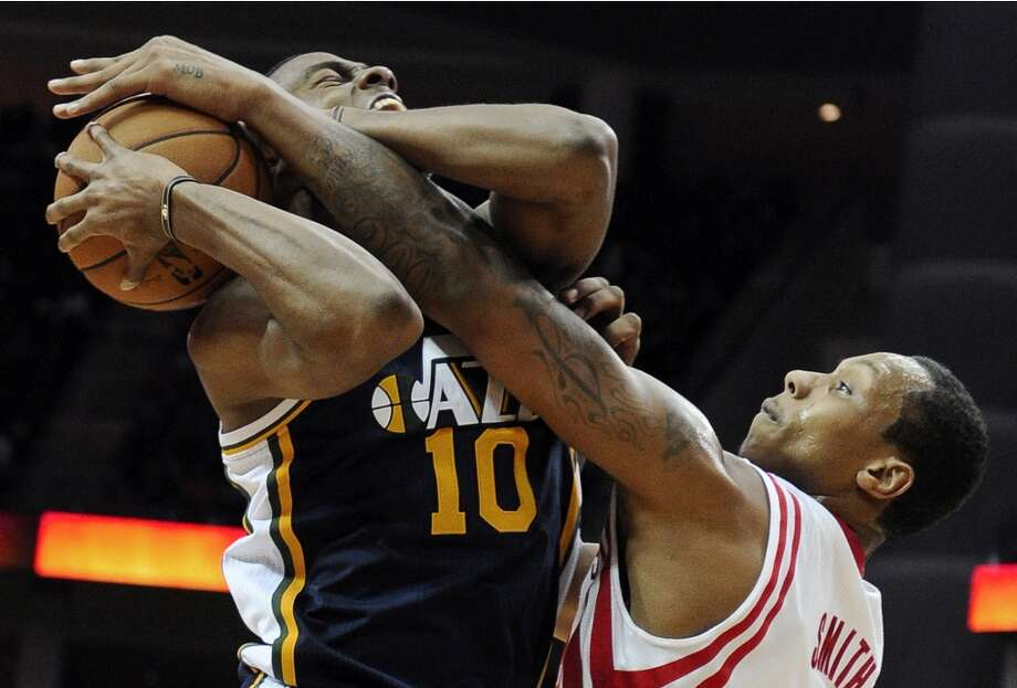Rockets' center Greg Smith knocks the ball away from Jazz forward Alec Burks in the second half. (Pat Sullivan / Associated Press)