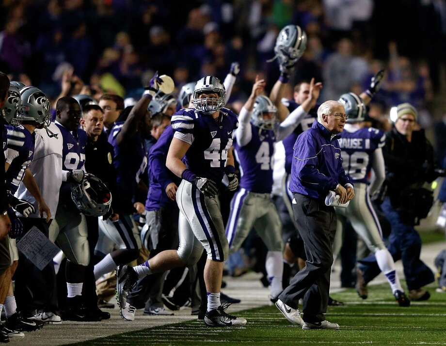 Head coach Bill Snyder of the Kansas State Wildcats walks onto the field as players celebrate following the Wildcats' 42-24 victory over the Texas Longhorns at Bill Snyder Family Football Stadium on December 1, 2012 in Manhattan, Kansas. Photo: Jamie Squire, Getty Images / 2012 Getty Images
