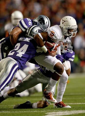 Running back Jeremy Hills #5 of the Texas Longhorns is tackled by defensive back Nigel Malone #24 and linebacker Jarell Childs #26 of the Kansas State Wildcats after making a catch during the game at Bill Snyder Family Football Stadium on December 1, 2012 in Manhattan, Kansas. Photo: Jamie Squire, Getty Images / 2012 Getty Images