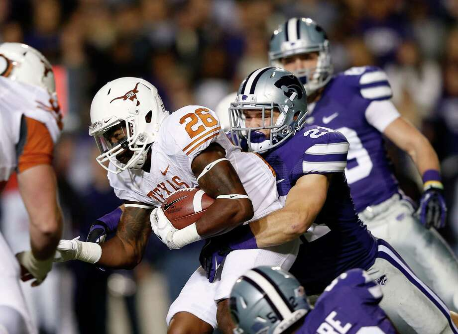 Running back D.J. Monroe #26 of the Texas Longhorns carries the ball as linebacker Jonathan Truman #21 of the Kansas State Wildcats defends during the game at Bill Snyder Family Football Stadium on December 1, 2012 in Manhattan, Kansas. Photo: Jamie Squire, Getty Images / 2012 Getty Images