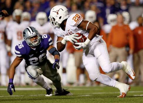 Running back Malcolm Brown #28 of the Texas Longhorns carries the ball as linebacker Jarell Childs #26 of the Kansas State Wildcats defends during the game at Bill Snyder Family Football Stadium on December 1, 2012 in Manhattan, Kansas. Photo: Jamie Squire, Getty Images / 2012 Getty Images