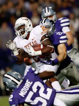 Running back D.J. Monroe #26 of the Texas Longhorns carries the ball as linebacker Jonathan Truman #21 and linebacker Mike Moore #52 of the Kansas State Wildcats defend during the game at Bill Snyder Family Football Stadium on December 1, 2012 in Manhattan, Kansas. Photo: Jamie Squire, Getty Images / 2012 Getty Images