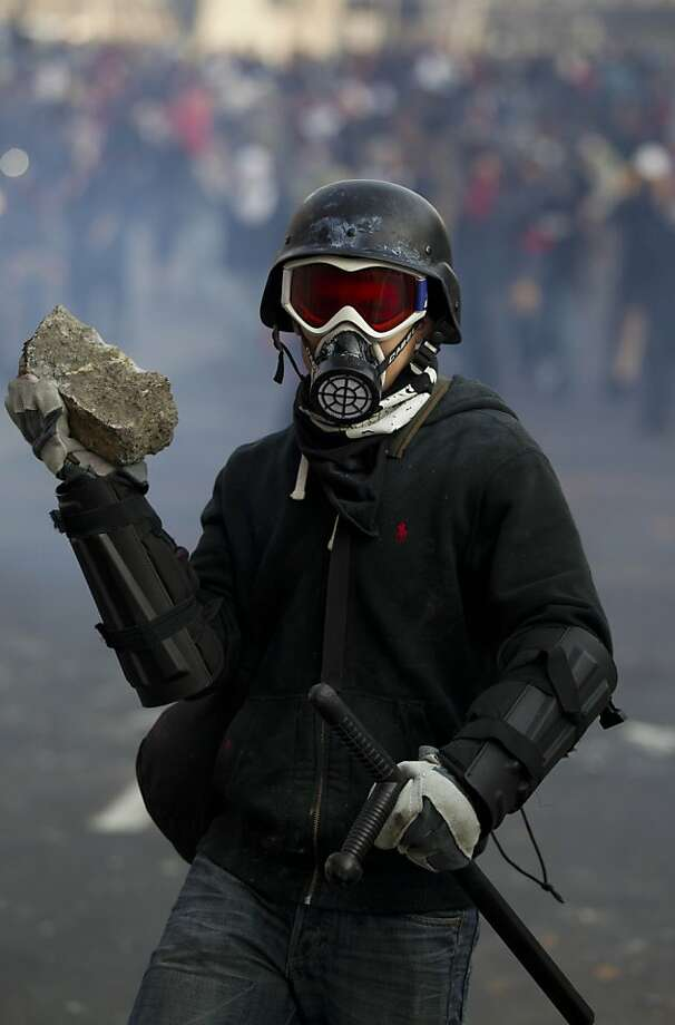A protestor holds a rock during clashes with police outside the steel security barriers around the National Congress, where the swearing in of new Mexican President Enrique Pena Nieto is taking place in Mexico City, Saturday Dec. 1, 2012. Pena Nieto took power at midnight in a symbolic ceremony and will formally take the oath of office Saturday morning after campaigning as the face of a new PRI, a party that claims to be repentant and reconstructed after voted out of the presidency in 2000. (AP Photo/Eduardo Verdugo) Photo: Eduardo Verdugo, Associated Press