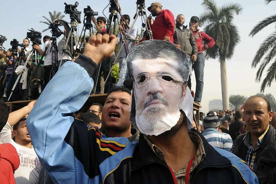 A supporter wears a mask depicting Egyptian President Mohammed Morsi at a rally in front of Cairo University in Cairo, Egypt, Saturday, Dec. 1, 2012. Tens of thousands of people waving Egyptian flags and hoisting large pictures of the president are demonstrating across Egypt Saturday in support of Morsi and Islamic law. The rally, organized by the Muslim Brotherhood, is seen as a test of strength for Islamists seeking to counteract large opposition protests held this past week by liberal and secular groups who the Brotherhood say do not represent the vast majority of Egyptians.(AP Photo/Mohammed Asad) Photo: Mohammed Asad, Associated Press