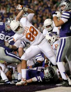 Kansas State quarterback Collin Klein, bottom, makes it into the end zone for a touchdown during the first half of an NCAA college football game against Texas, Saturday, Dec. 1, 2012, in Manhattan, Kan. (AP Photo/Charlie Riedel) Photo: Charlie Riedel, Associated Press / AP
