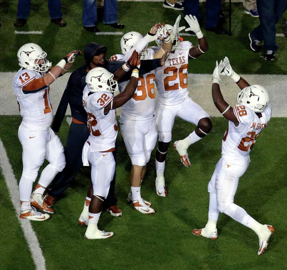 Texas running back Malcolm Brown (28) celebrates with teammates after scoring a touchdown during the second half of an NCAA college football game against Kansas State, Saturday, Dec. 1, 2012, in Manhattan, Kan. (AP Photo/Charlie Riedel) Photo: Charlie Riedel, Associated Press / AP