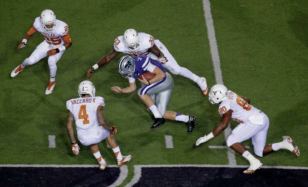 Kansas State quarterback Collin Klein (7) is chased by Texas defenders Josh Turner (25), Kenny Vaccaro (4), Steve Edmond (33) and Alex Okafor (80) during the first half of an NCAA college football game on Saturday, Dec. 1, 2012, in Manhattan, Kan. (AP Photo/Charlie Riedel)