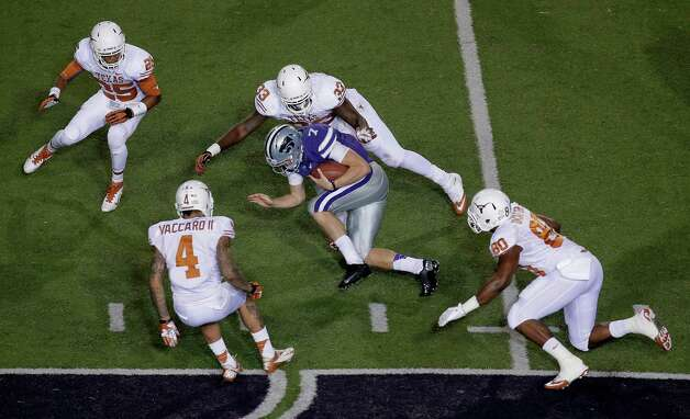 Kansas State quarterback Collin Klein (7) is chased by Texas defenders Josh Turner (25), Kenny Vaccaro (4), Steve Edmond (33) and Alex Okafor (80) during the first half of an NCAA college football game on Saturday, Dec. 1, 2012, in Manhattan, Kan. (AP Photo/Charlie Riedel) Photo: Charlie Riedel, Associated Press / AP
