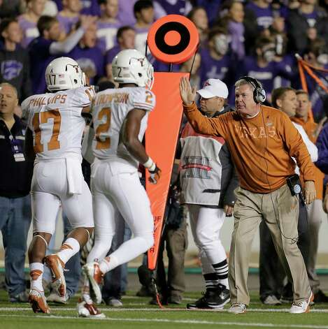 Texas coach Mack Brown, right, celebrates with cornerback Adrian Phillips (17) and defensive back Mykkele Thompson (2) after Phillips intercepted a pass during the first half of an NCAA college football game against Kansas State, Saturday, Dec. 1, 2012, in Manhattan, Kan. (AP Photo/Charlie Riedel) Photo: Charlie Riedel, Associated Press / AP