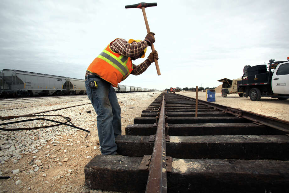 Jose Moreno of Alamo Railroad Inc., drives spikes in a new section of track at Texas Gonzales and Northern Railway.  Operations at the Texas Gonzales and Northern Railway, just outside of Gonzales, Texas have taken off due to the increased business from the Eagle Ford.  Tuesday, Nov. 13, 2012. Photo: Bob Owen, San Antonio Express-News / © 2012 San Antonio Express-News