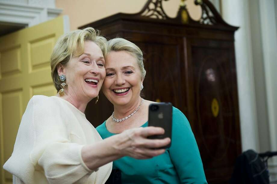 Actress Meryl Streep uses her iPhone to get a photo of her and Secretary of State Hillary Rodham Clinton following the State Department Dinner for the Kennedy Center Honors gala Saturday, Dec. 1, 2012 at the State Department in Washington. (AP Photo/Kevin Wolf) Photo: Kevin Wolf, Associated Press