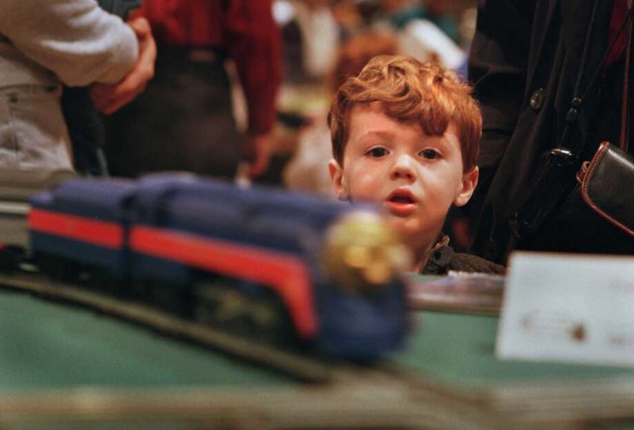 Times Union photo by PAUL BUCKOWSKI -- SUNDAY DECEMBER 7 1997 -- ALBANY NY -- GREAT TRAIN EXTRAVAGANZA --  Three year old Aidan Coyle, of Guilderland, watches one of the many trains at the 1997 Great Train Extravanganza at the Empire State Plaza Convention Center go around a track Sunday morning. (DG)