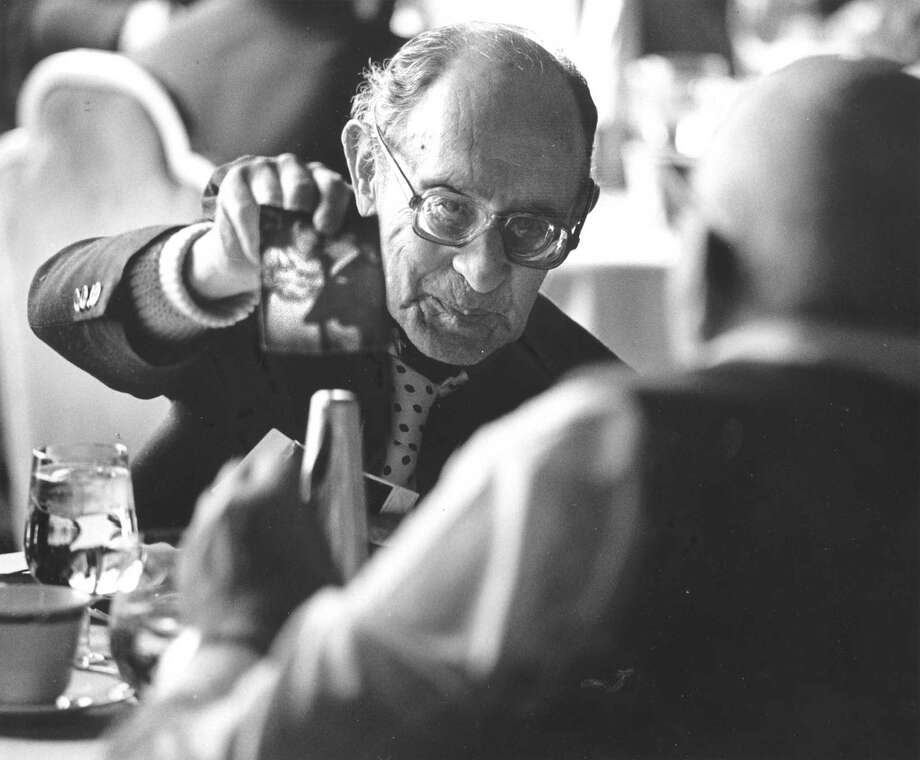 At the annual holiday for seniors held at Giovanni's Steak Pub on Dec. 3, 1987, Sanford J. Cahn, of Stamford, shows a photograph to Trumbull resident to John Schlechtweg. Photo: Advocate