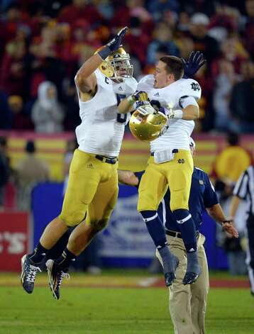 Notre Dame linebacker Manti Te'o, left, celebrates with wide receiver Robby Toma in the closing seconda of an NCAA college football game against Southern California, Saturday, Nov. 24, 2012, in Los Angeles. Notre Dame won 22-13. (AP Photo/Mark J. Terrill) Photo: Mark J. Terrill, Associated Press / AP