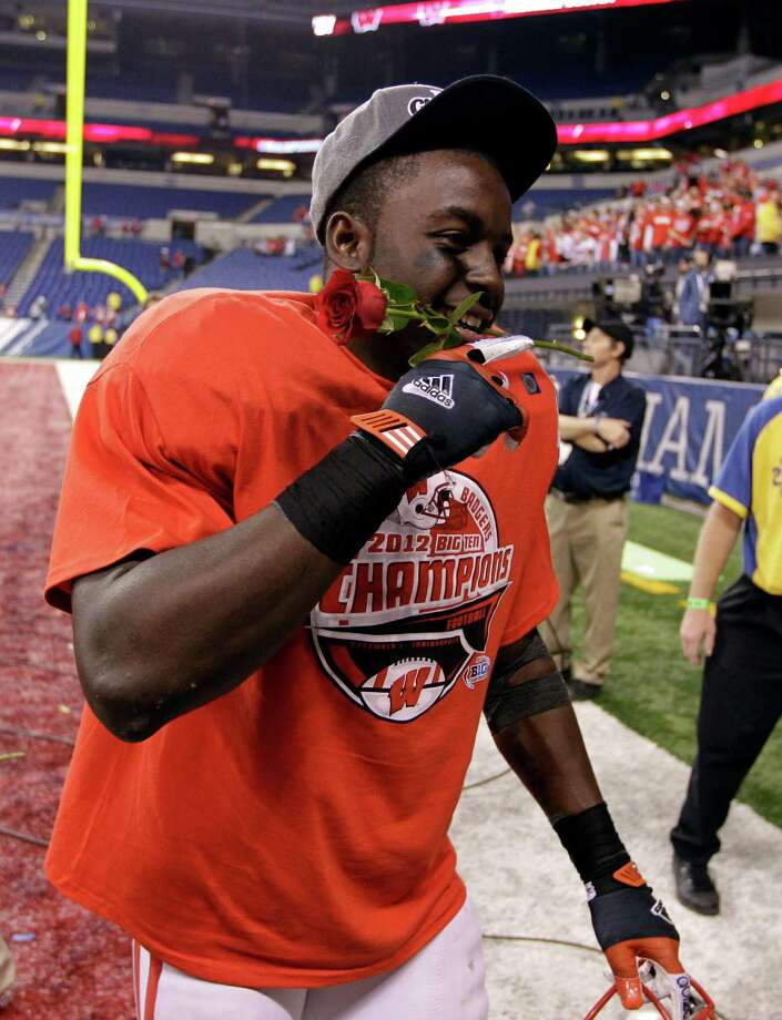 Wisconsin running back Montee Ball holds a rose in his mouth after Wisconsin defeated Nebraska to win the Big Ten Conference championship NCAA college football game Saturday, Dec. 1, 2012, in Indianapolis. (AP Photo/Michael Conroy) Photo: Michael Conroy, Associated Press / AP