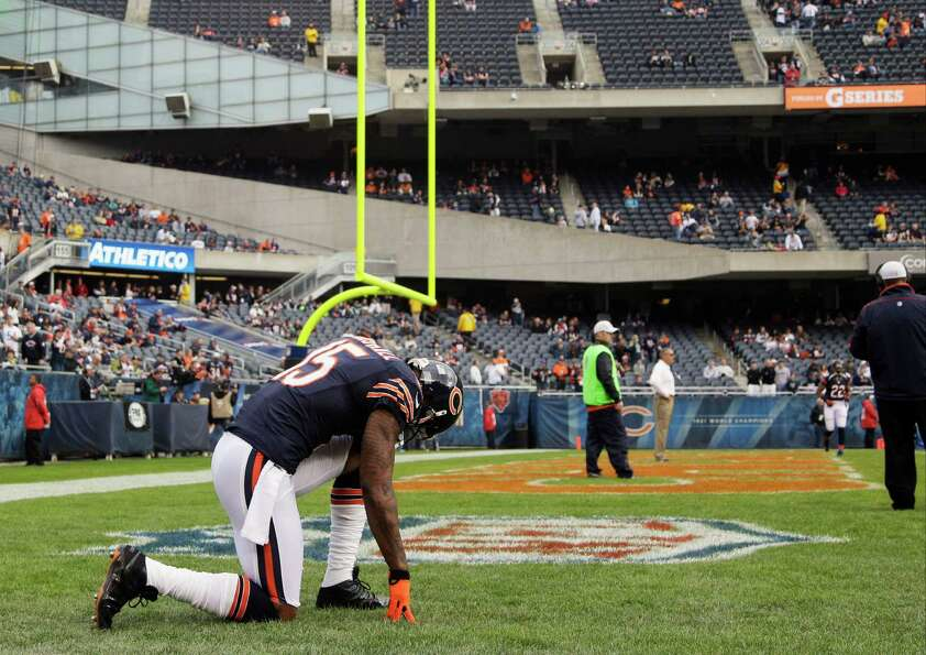 Chicago Bears wide receiver Brandon Marshall (15) kneels down on the field during warmups before an