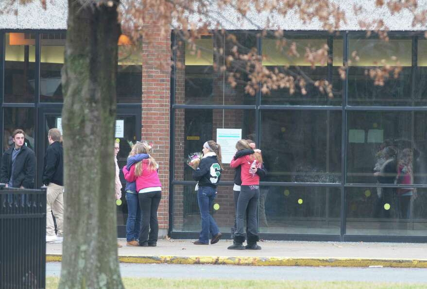 Students embrace each other Sunday outside the Shenendehowa High School East building in Clifton Par