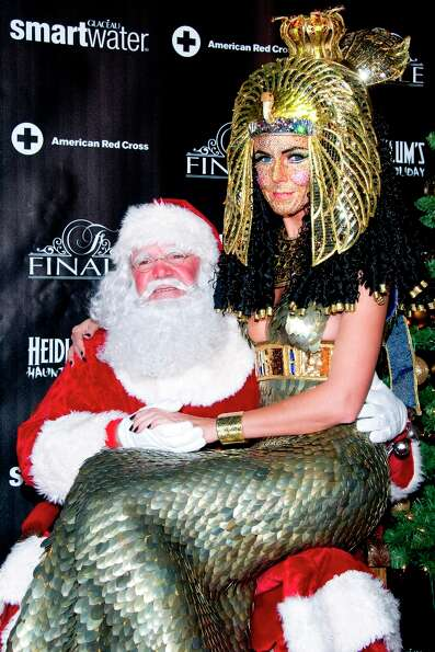 Heidi Klum, dressed as Cleopatra, poses with Santa Claus during her Haunted Holiday Party benefiting