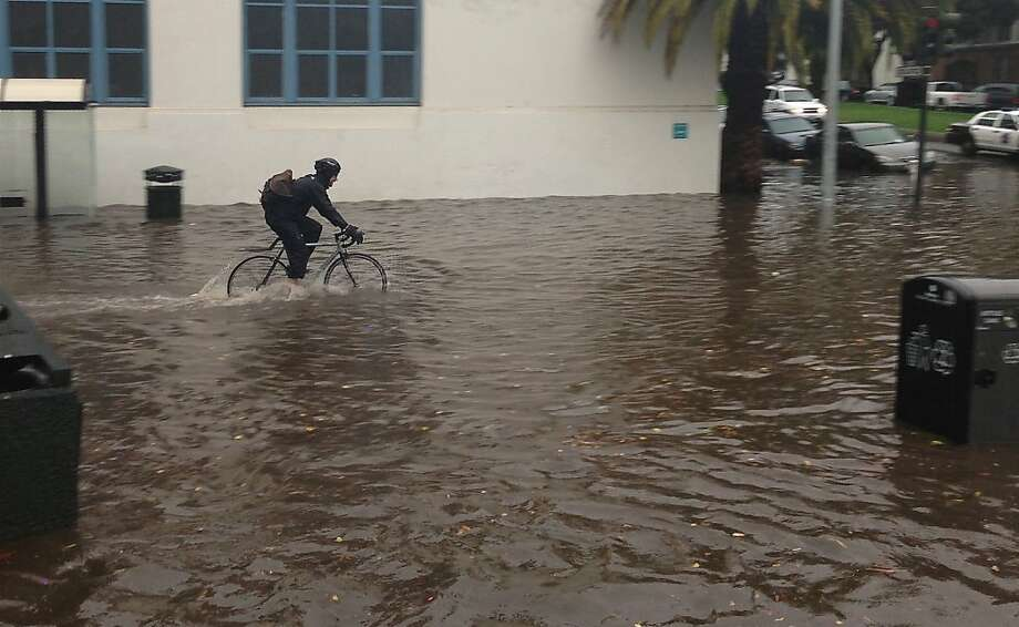A bicyclist makes his way through water at the intersection of 18th and Dolores streets at the base of Dolores Park on Sunday, December 2, 2012. Water pouring down both streets and the hills of the park all converged at the intersection. Photo: Jeff Elder, The Chronicle