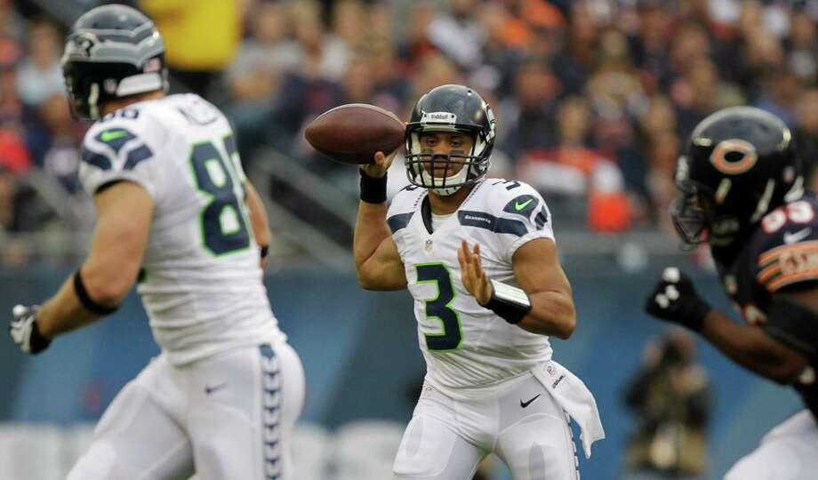 Seattle Seahawks quarterback Russell Wilson (3) passes to tight end Zach Miller (86) in the first half of an NFL football game against the Chicago Bears in Chicago, Sunday, Dec. 2, 2012. at right is  Bears Nick Roach (53). Photo: AP